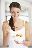 Junge Frau, die frischen Fruchtsalat isst Stockbilder