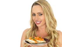 Junge Frau, die Frischkäse des Lachs- und auf einem Cracker isst Stockfoto