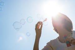 Junge Frau, die froh einen Strom von Seifenblasen durchbrennt Stockfoto
