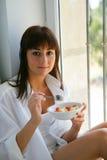 Junge Frau, die Frucht in einer Schüssel isst Stockbilder