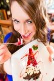 Junge Frau, die Fruchtkuchen am Café oder an der Bäckerei isst Lizenzfreie Stockfotos