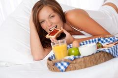 Junge Frau, die gebildetes Haupt frühstückt stockfotografie