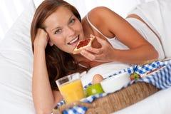 Junge Frau, die gebildetes Haupt frühstückt stockfotos