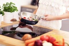 Junge Frau, die gebratenes Gemüse in der Küche vorbereitet Stockbilder