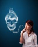 Junge Frau, die gefährliche Zigarette mit giftigem Schädelrauche raucht Stockfoto
