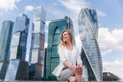 Junge Frau, die gegen Büro buidings sitzt Lizenzfreies Stockbild