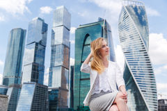 Junge Frau, die gegen Büro buidings sitzt Lizenzfreie Stockfotos