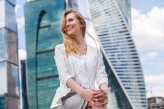 Junge Frau, die gegen Büro buidings sitzt Lizenzfreie Stockbilder