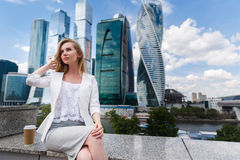 Junge Frau, die gegen Büro buidings sitzt Stockbild