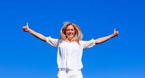 Junge Frau, die gegen blauen Himmel springt Stockfotografie
