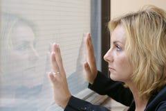 Junge Frau, die gegen Hartglas steht. Stockbild