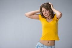 Junge Frau, die gelbes Hemd und kurze Jeanshose über grauem BAC trägt Lizenzfreie Stockfotos