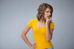 Junge Frau, die gelbes Hemd und kurze Jeanshose über grauem BAC trägt Stockbilder