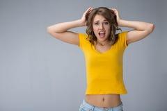 Junge Frau, die gelbes Hemd und kurze Jeanshose über grauem BAC trägt Stockfoto