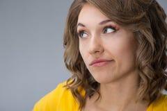 Junge Frau, die gelbes Hemd und kurze Jeanshose über grauem BAC trägt Lizenzfreies Stockbild