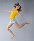Junge Frau, die gelbes Hemd und kurze Jeanshose über grauem BAC trägt Stockfotografie
