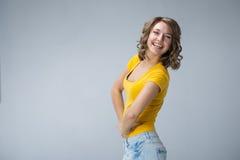 Junge Frau, die gelbes Hemd und kurze Jeanshose über grauem BAC trägt Stockfotos