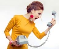 Junge Frau, die gelbes Kleid im Retrostil mit altem Telefon trägt stockbild