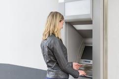 Junge Frau, die Geld an einem ATM zurücknimmt Lizenzfreie Stockfotografie