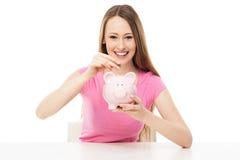 Junge Frau, die Geld in piggy Querneigung einsetzt Stockfoto