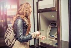 Junge Frau, die Geld von ATM nimmt Stockfoto