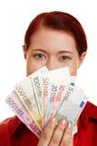 Junge Frau, die Geldgebläse zeigt Stockfotos
