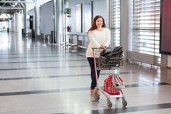 Junge Frau, die Gepäckwagen im Flughafen zieht Stockfoto