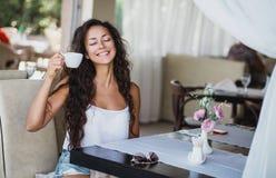 Junge Frau, die Geruch des Kaffees genießt Stockfoto