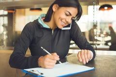 Junge Frau, die gesunden Lebensstil der Innensportkleidung sitzt Stockfotografie