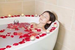 Junge Frau, die am Gesundheits-Badekurort badet Stockbild