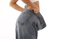 Junge Frau, die Gewichtverlust vorführt Stockfotos