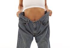 Junge Frau, die Gewichtverlust vorführt Lizenzfreie Stockfotografie