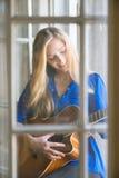 Junge Frau, die Gitarre auf Fenster spielt Lizenzfreies Stockfoto