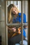 Junge Frau, die Gitarre auf Fenster spielt Lizenzfreie Stockfotografie