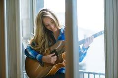 Junge Frau, die Gitarre auf Fenster spielt Stockfotos