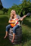 Junge Frau, die Gitarre im Weinberg spielt Stockfotografie