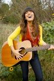 Junge Frau, die Gitarre singt und spielt Stockbild