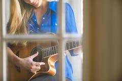 Junge Frau, die Gitarre spielt Lizenzfreies Stockfoto