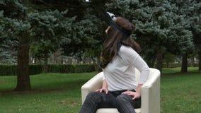 Junge Frau, die Gläser der virtuellen Realität im Park herum schaut während trockenes Blattfallen verwendet stock video footage