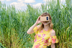 Junge Frau, die Gläser einer virtuellen Realität untersucht Stockfotos