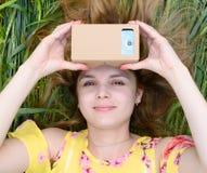 Junge Frau, die Gläser einer virtuellen Realität untersucht Lizenzfreies Stockfoto