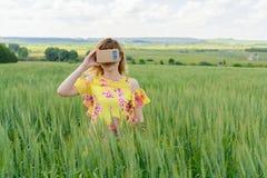 Junge Frau, die Gläser einer virtuellen Realität untersucht Stockbilder
