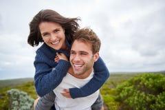 Junge Frau, die glücklich beim durch ihr boyfr huckepack getragen werden lächelt stockbild