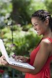 Junge Frau, die glücklich draußen an einem Laptop arbeitet Stockfotografie