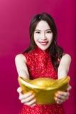 junge Frau, die Gold für chinesisches neues Jahr zeigt Lizenzfreies Stockfoto