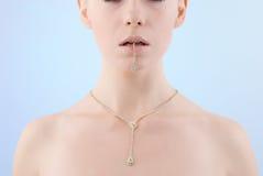 Junge Frau, die goldenes Armband in ihrem Mund anhält Lizenzfreies Stockbild
