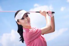 Junge Frau, die Golf spielt Stockfotos