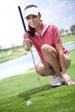 Junge Frau, die Golfclubs hält Lizenzfreies Stockfoto