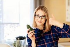Junge Frau, die grüne Avocado in der Küche hält lizenzfreies stockfoto