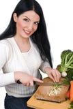Junge Frau, die grüne Zwiebel hackt Lizenzfreies Stockbild